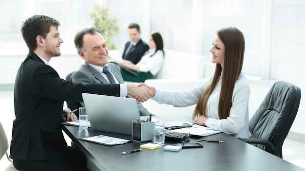 Młoda biznesowa kobieta, ściskając ręce z dorosłym partnerem biznesowym.
