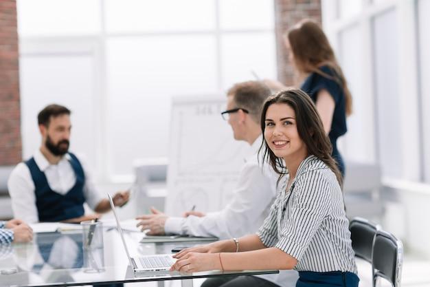 Młoda biznesowa kobieta siedzi przy biurku. pomysł na biznes