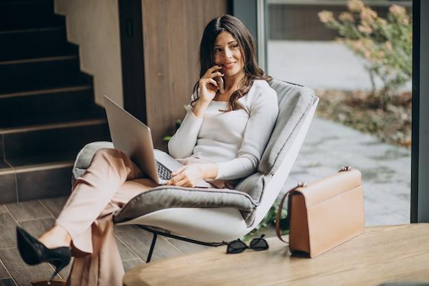 Młoda biznesowa kobieta siedzi w cahir i pracuje na komputerze