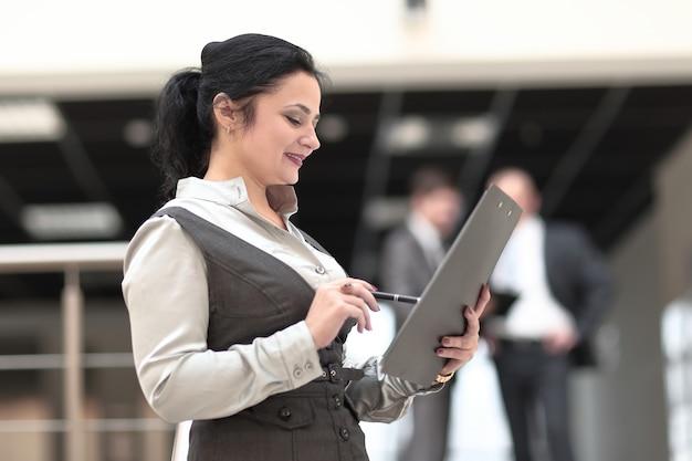 Młoda biznesowa kobieta studiuje dokument roboczy