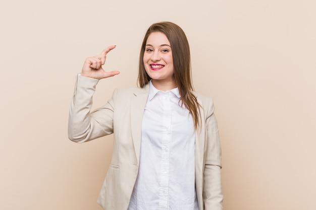 Młoda biznesowa kobieta trzyma coś trochę z forefingers, uśmiechnięta i ufna.