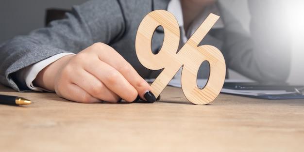 Młoda biznesowa kobieta trzyma drewniany procent.