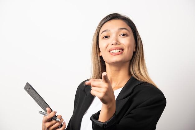 Młoda biznesowa kobieta trzyma schowek i wskazuje