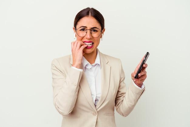 Młoda biznesowa kobieta trzyma telefon komórkowy na białym tle gryząc paznokcie, nerwowy i bardzo niespokojny.