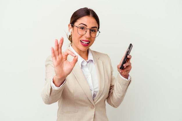 Młoda biznesowa kobieta trzyma telefon komórkowy na białym tle wesoły i pewny siebie, pokazując gest ok.