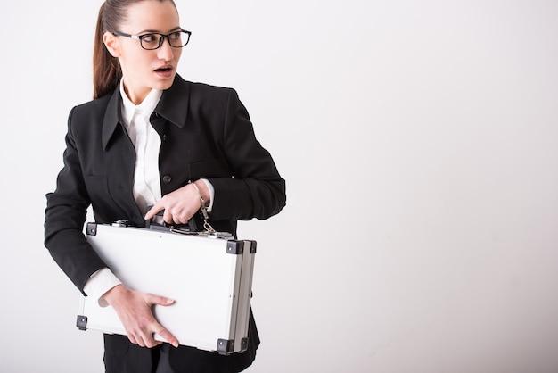 Młoda biznesowa kobieta ucieka z walizką.