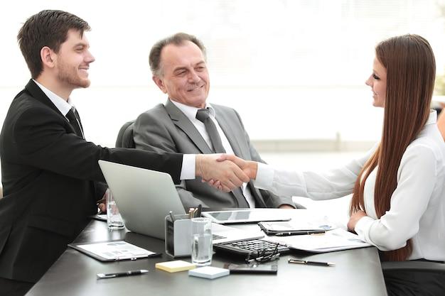 Młoda biznesowa kobieta uścisk dłoni z dorosłym partnerem biznesowym.