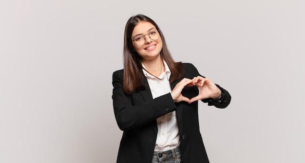 Młoda biznesowa kobieta uśmiecha się i czuje się szczęśliwa, urocza, romantyczna i zakochana, tworząc kształt serca obiema rękami