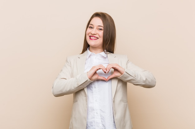 Młoda biznesowa kobieta uśmiecha się i pokazuje kształt serca rękami.