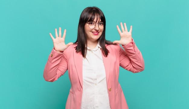 Młoda biznesowa kobieta uśmiecha się i wygląda przyjaźnie, pokazując liczbę dziesięć lub dziesiątą ręką do przodu, odliczając w dół