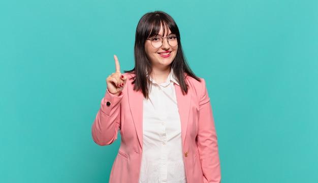 Młoda biznesowa kobieta uśmiecha się i wygląda przyjaźnie, pokazując numer jeden lub pierwszy z ręką do przodu, odliczając w dół