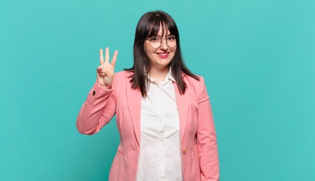 Młoda biznesowa kobieta uśmiecha się i wygląda przyjaźnie, pokazując numer trzy lub trzeci z ręką do przodu, odliczając w dół