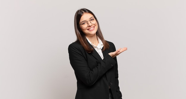 Młoda biznesowa kobieta uśmiecha się radośnie, czuje się szczęśliwa i pokazuje koncepcję w przestrzeni kopii z dłonią