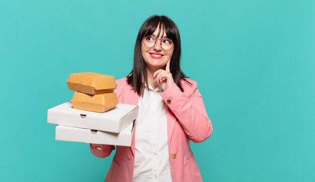 Młoda biznesowa kobieta uśmiecha się radośnie i marzy lub wątpi, patrząc w bok