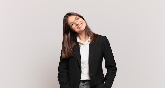 Młoda biznesowa kobieta uśmiecha się radośnie i od niechcenia z pozytywnym, szczęśliwym, pewnym siebie i zrelaksowanym wyrazem twarzy