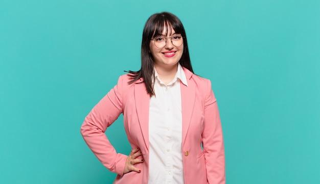 Młoda biznesowa kobieta uśmiecha się radośnie z ręką na biodrze i pewna siebie, pozytywna, dumna i przyjazna postawa