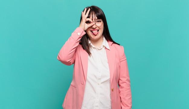 Młoda biznesowa kobieta uśmiecha się radośnie ze śmieszną miną, żartuje i patrzy przez wizjer, szpiegując sekrety