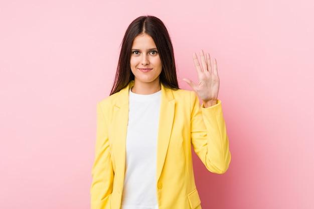 Młoda biznesowa kobieta uśmiecha się rozochoconego seans liczba pięć z palcami.