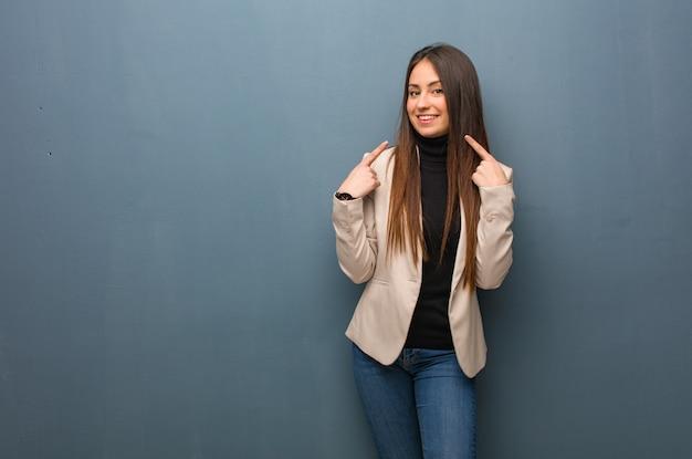 Młoda biznesowa kobieta uśmiecha się, wskazując usta