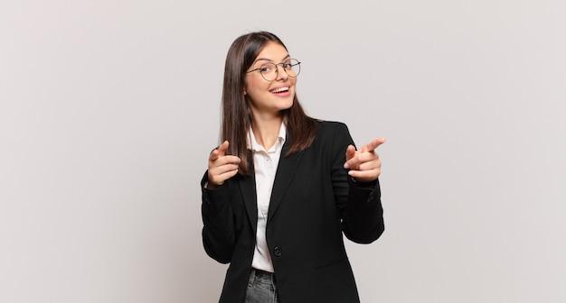 Młoda biznesowa kobieta uśmiecha się z pozytywnym, odnoszącym sukcesy, szczęśliwym nastawieniem, wskazując na kamerę, robiąc znak pistoletu rękami