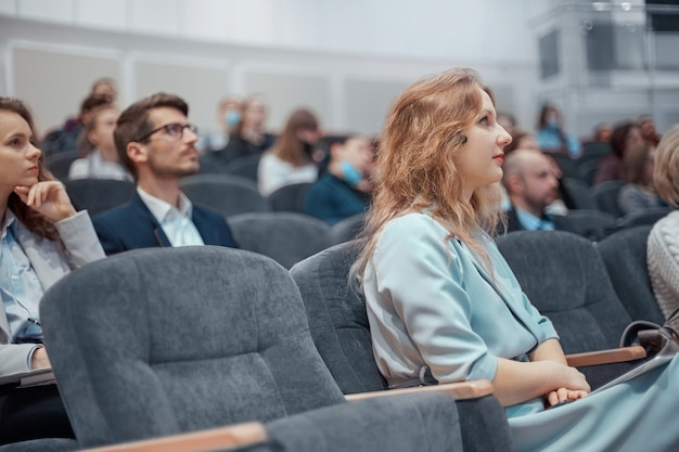 Młoda biznesowa kobieta uważnie słucha mówcy