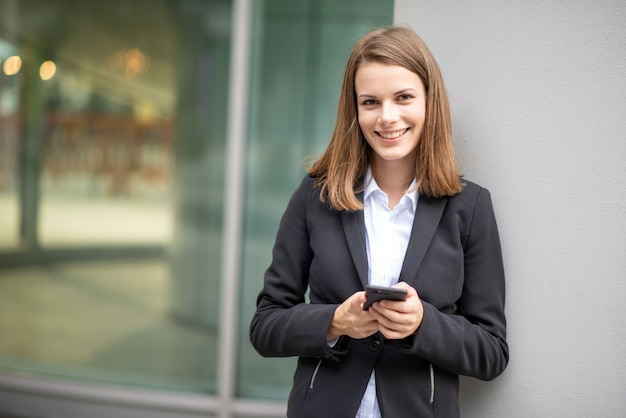 Młoda biznesowa kobieta używa jej mobilnego telefon komórkowego