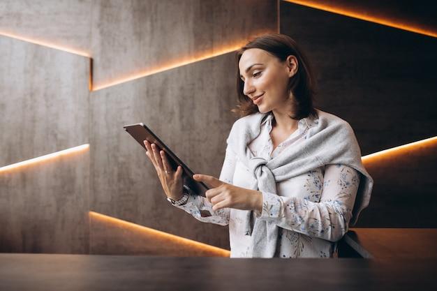 Młoda biznesowa kobieta używa pastylkę