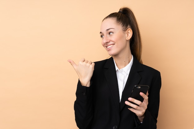 Młoda biznesowa kobieta używa telefon komórkowego nad odosobnioną ścianą wskazuje strona przedstawiać produkt
