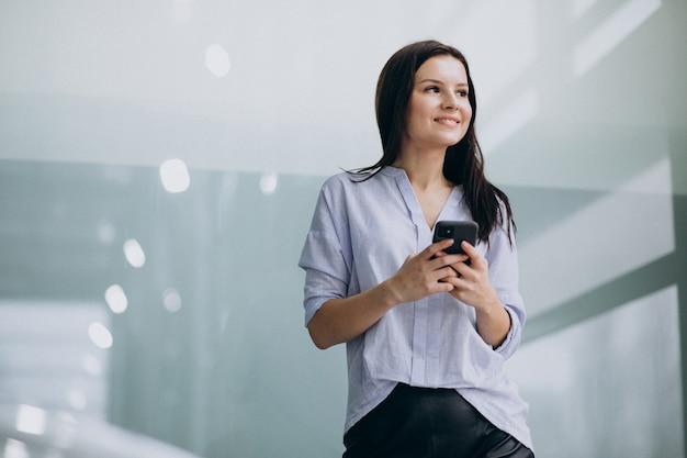 Młoda biznesowa kobieta używa telefon przy biurem