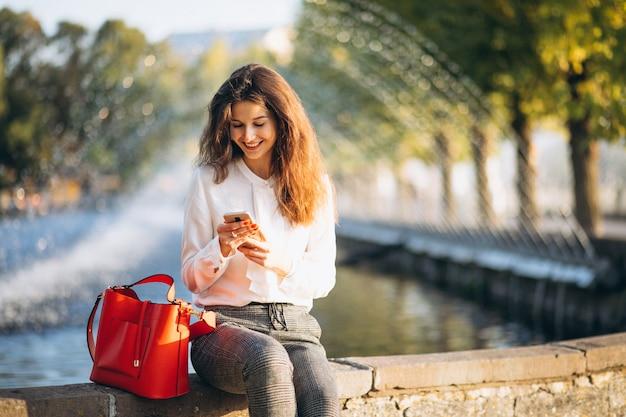 Młoda biznesowa kobieta używa telefon w parku przy lunchu czasem