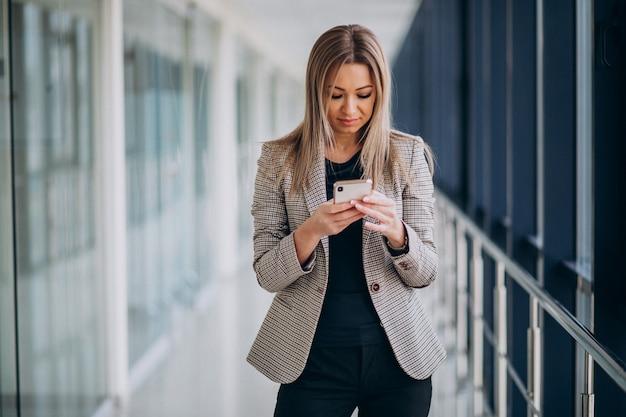 Młoda biznesowa kobieta używa telefon w terminal