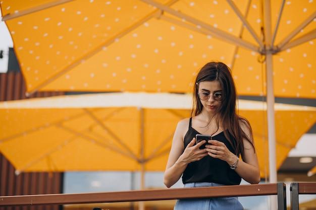 Młoda biznesowa kobieta używa telefonu na wakacjach