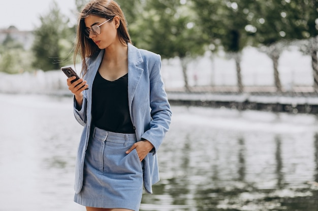 Młoda biznesowa kobieta używa telefonu w parku