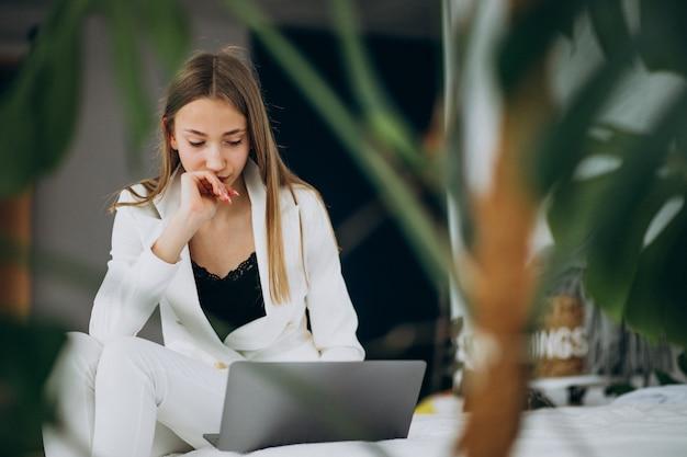 Młoda biznesowa kobieta w białym kostiumu pracuje na komputerze