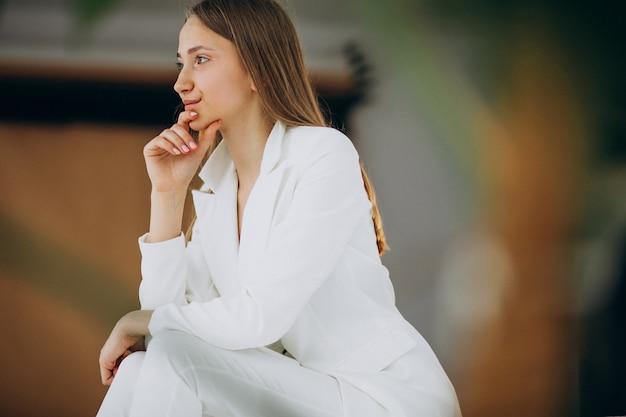 Młoda biznesowa kobieta w białym kostiumu przy studiiem