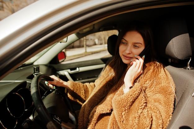 Młoda biznesowa kobieta w futrze siedzi za kierownicą samochodu i mówić na telefon komórkowy.