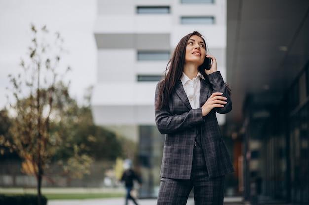 Młoda biznesowa kobieta w klasycznym garniturze przez centrum biurowe
