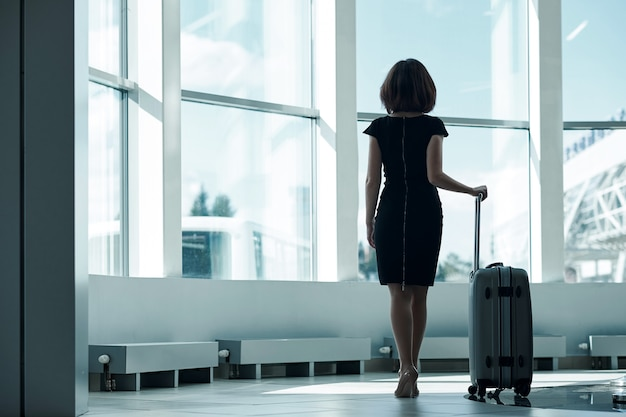 Młoda biznesowa kobieta w lotnisku z bagażem, czeka odjazd