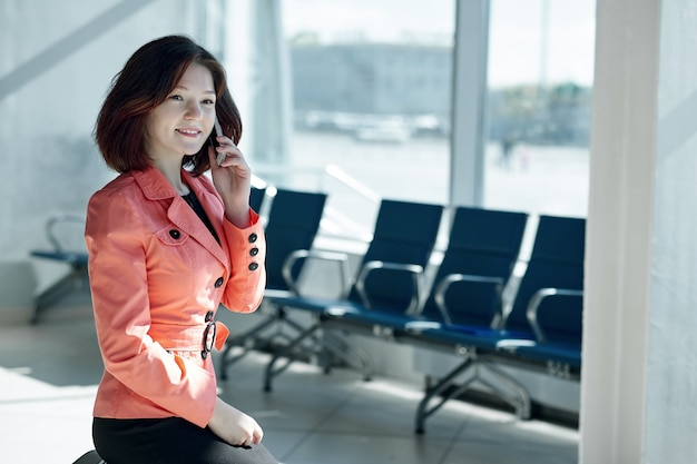 Młoda biznesowa kobieta w lotnisku z bagażem, rozmawia przez telefon i ono uśmiecha się.
