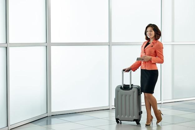 Młoda biznesowa kobieta w lotnisku z bagażową tramwaj torbą, czeka odjazd