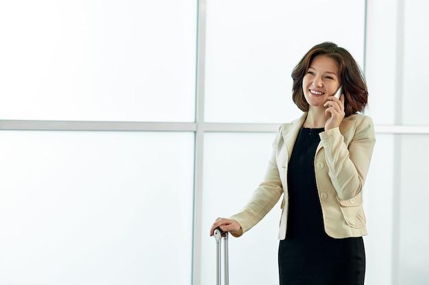 Młoda biznesowa kobieta w lotnisku z bagażową tramwaj torbą, opowiada przez telefonu i ono uśmiecha się.