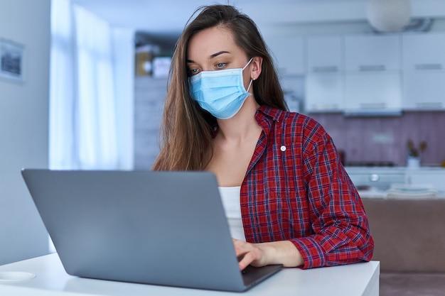 Młoda biznesowa kobieta w medycznej masce ochronnej pracuje z domu przy komputerze podczas samoizolacji i kwarantanny.