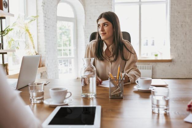 Młoda biznesowa kobieta w nowoczesnym biurze z zespołem. kreatywne spotkanie, dyskusja, praca nad projektem. pojęcie finansów, biznesu, girl power, integracji, różnorodności, feminizmu. wygląda na szczęśliwego i zadbanego.