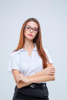 Młoda biznesowa kobieta w okularach na szarym tle