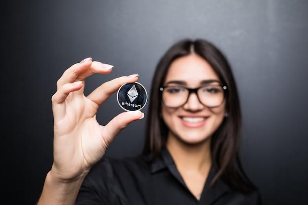 Młoda biznesowa kobieta w okularach z litecoin w rękach na białym tle na czarnej ścianie.