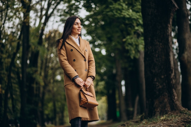 Młoda biznesowa kobieta w płaszczu spaceru w parku