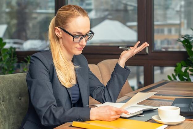 Młoda biznesowa kobieta w szkłach siedzi przy miejscem pracy i czyta papiery przy biurem