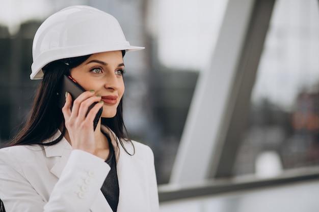 Młoda biznesowa kobieta w twardym kapeluszu przy obiekcie budowlanym