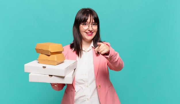 Młoda biznesowa kobieta wskazująca na aparat z zadowolonym, pewnym siebie, przyjaznym uśmiechem, wybierająca ciebie