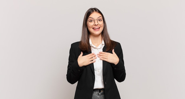Młoda biznesowa kobieta wygląda na szczęśliwą, zaskoczoną, dumną i podekscytowaną, wskazując na siebie